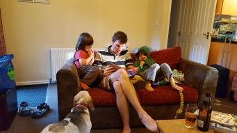 Phil reading a story to the boys and Lottie